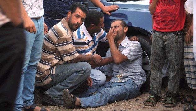 Ein verzweifelter Angehöriger wartet auf Nachrichten über das gekenterte Flüchtlingsboot. (Bild: EPA)