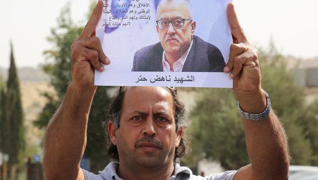Ein Demonstrant hält ein Bild des getöteten Autors hoch, um seiner zu gedenken. (Bild: AP)