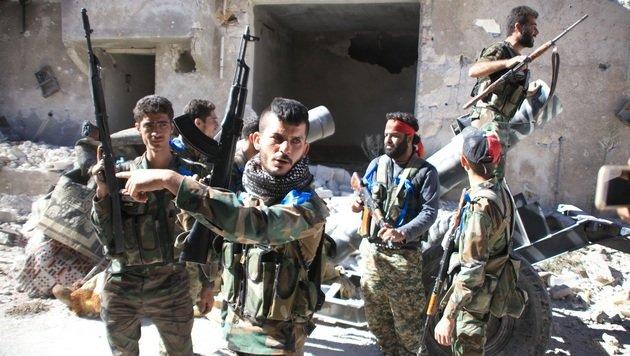 Syrische Truppen nach der Rückeroberung eines Flüchtlingslagers nördlich von Aleppo (Bild: APA/AFP/GEORGE OURFALIAN)