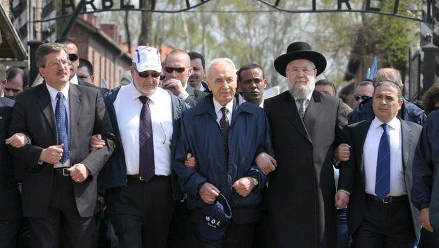 Peres mit Polens Ex-Premier Bronislaw Komorowski (1. v. links) während eines Besuchs in Auschwitz (Bild: EPA)