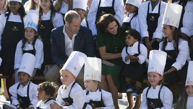 Prinz William und Herzogin Kate umringt von kleinen Köchen, die für das Prinzenpaar gekocht haben. (Bild: AP)