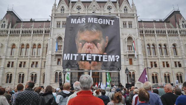 """""""Was habe ich schon wieder getan?"""", lassen Demonstranten Orban auf diesem Plakat fragen. (Bild: Associated Press)"""