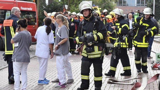 Feuerwehrmänner und Spitalspersonal nach der Evakuierung des Krankenhauses (Bild: ASSOCIATED PRESS)