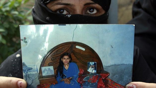 Die Mutter von Tasleem Solangi zeigt ein Bild ihrer Tochter, die Opfer eines Ehrenmordes wurde. (Bild: AP)