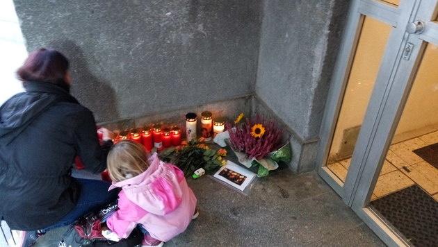 Blumen und Kerzen vor dem Wohnhaus der Opfer in Wien (Bild: APA/ANDREAS WESTPHAL)