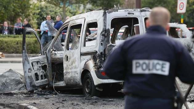 Die zwei Polizeiautos brannten komplett aus. (Bild: APA/AFP/THOMAS SAMSON)