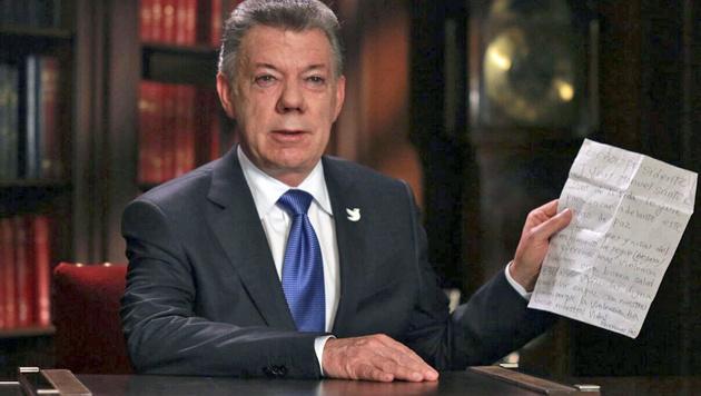 Präsident Santos mit einem Brief, in dem ihn ein Mädchen bittet, die Friedensbemühungen fortzusetzen (Bild: APA/AFP/PRESIDENCIA COLOMBIA/HO)