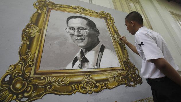 Ein thailändischer Schüler beim Verzieren eines Porträts des verstorbenen Königs Bhumibol (Bild: ASSOCIATED PRESS)
