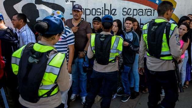 Polizisten überwachen Menschen, die vor einem Lebensmittelgeschäft in Caracas Schlange stehen. (Bild: APA/AFP/FEDERICO PARRA)