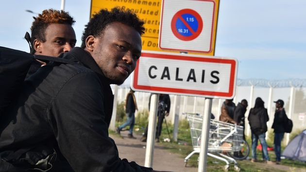 Wartende Migranten vor den Toren des geräumten Lagers in Calais (Bild: APA/AFP/PHILIPPE HUGUEN)
