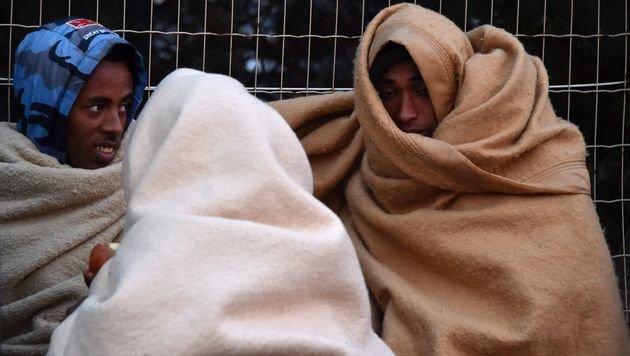 In Decken gehüllte Flüchtlinge nach der Räumung des Lagers von Calais (Bild: APA/AFP/PHILIPPE HUGUEN)
