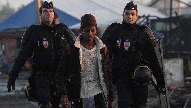 Ein junger Flüchtling wird von zwei französischen Polizisten aus dem Lager von Calais begleitet. (Bild: ASSOCIATED PRESS)