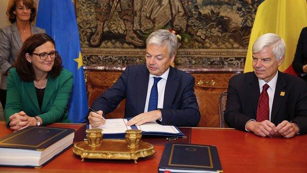 Didier Reynders (Mitte) bei der Unterzeichnung des Pakts. (Bild: APA/AFP/Belga/ Nicolas Maeterlinck)
