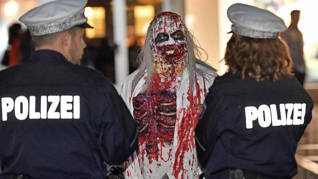 Ein Teilnehmer des Zombie-Walk in Essen mit zwei Polizisten (Bild: Associated Press)
