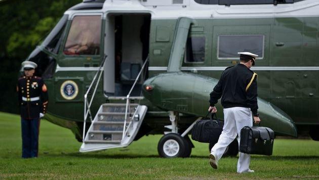 Ein Militäradjutant trägt den Atomkoffer in seiner rechten Hand zum Hubschrauber des US-Präsidenten. (Bild: APA/AFP/BRENDAN SMIALOWSKI)