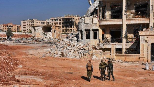Prosyrische Soldaten in der total zerstörten Stadt (Bild: APA/AFP/George Ourfalian)