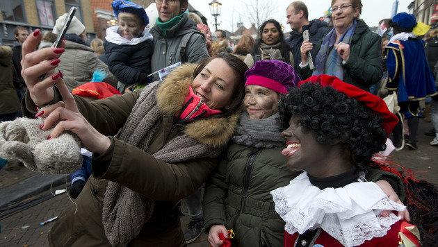 """Den Menschen gefallen die """"Zwarten Pieten"""", viele halten die Schminke der Helfer für rassistisch. (Bild: ASSOCIATED PRESS)"""