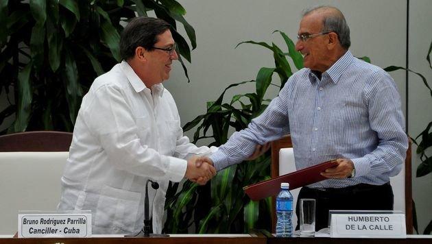 Kubas Außenminister Bruno Rodriguez Parrilla gratuliert Verhandlungsführer Humberto de la Calle. (Bild: APA/AFP/YAMIL LAGE)