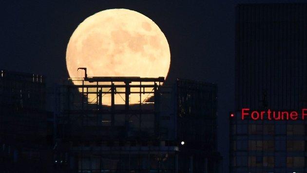 Der Supermond über Peking (Bild: APA/AFP/Greg Baker)
