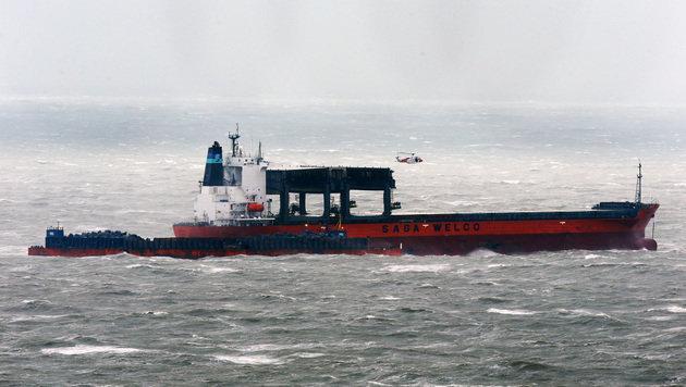 """Ein Hubschrauber der Küstenwache beobachtet den Rettungseinsatz an Bord des Frachters """"Saga Sky"""". (Bild: ASSOCIATED PRESS)"""
