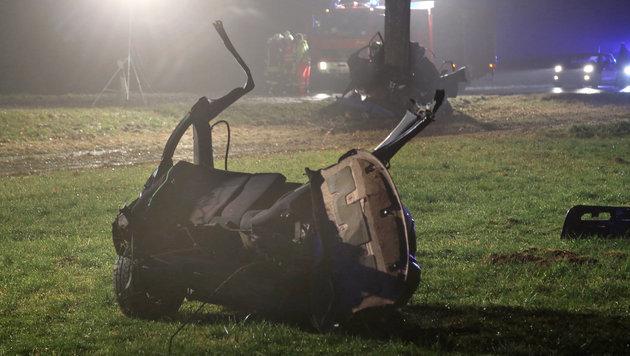 Ein Teil des zerstörten Autos liegt auf einer Wiese, die andere Hälfte ist im Hintergrund zu sehen. (Bild: APA/dpa/Thomas Poppel)