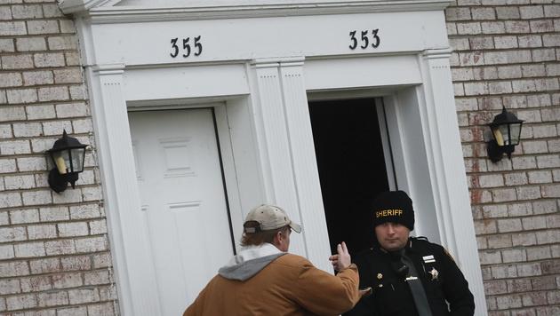Ermittler vor dem Wohnhaus des Täters (Bild: AP)