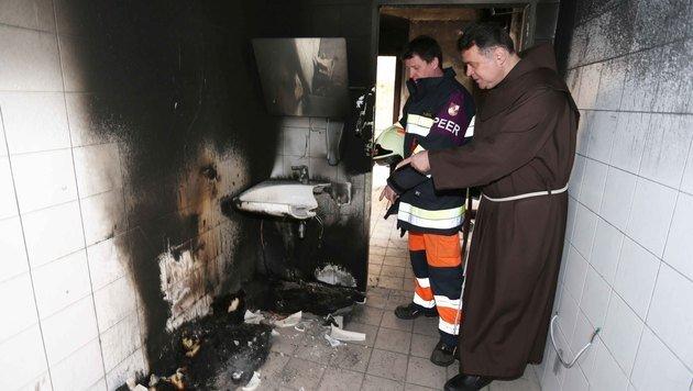 Pater Thomas vor der abgefackelten Toilette (Bild: Reinhard Judt)