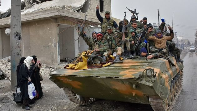 Regierungstruppen auf dem Weg nach Ost-Aleppo treffen auf Flüchtende. (Bild: APA/AFP/GEORGE OURFALIAN)