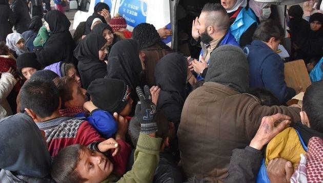 Geflohene Familien bei der Essensausgabe in einem Vorort von Aleppo (Bild: APA/AFP/GEORGE OURFALIAN)