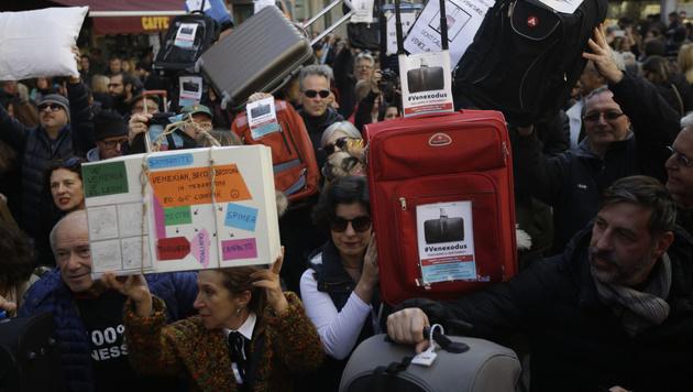 Mit Koffern demonstrieren die Bewohner der Lagungenstadt gegen die Touristenmassen. (Bild: APA/AFP/MARCO BERTORELLO)