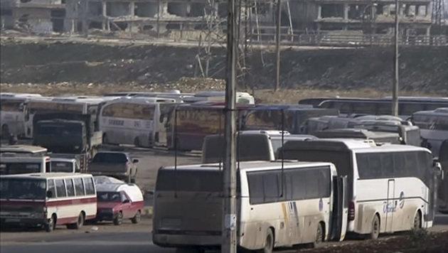 Busse, die auf flüchtende Zivilisten warten (Bild: ASSOCIATED PRESS)