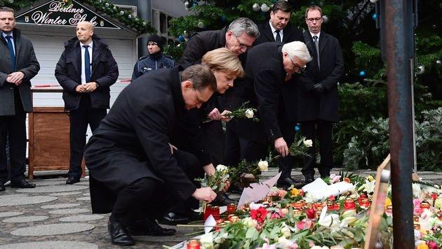Außenminister Steinmeier und Innenminister De Maiziere besuchten zusammen mit Merkel den Tatort. (Bild: APA/AFP/TOBIAS SCHWARZ)