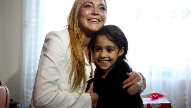 Lindsay Lohan mit einem Flüchtlingskind in einem Camp in der Türkei (Bild: Viennareport)
