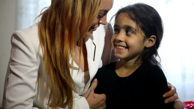 Lindsay Lohan mit einem syrischen Flüchtlingsmädchen (Bild: Viennareport)