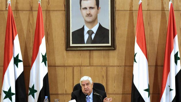 """Syriens Außenminister Muallem unter einem Bild seines """"Chefs"""", Präsident Bashar al-Assad (Bild: APA/AFP/LOUAI BESHARA)"""