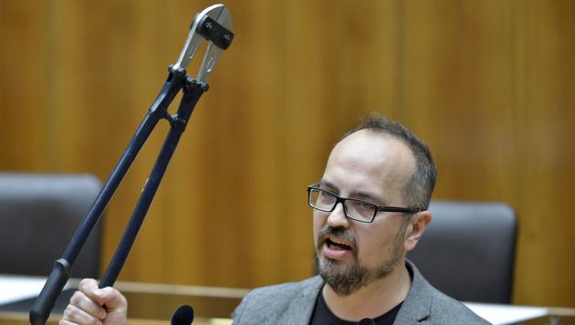 Der EU-Abgeordnete Michel Reimon verteilte Bolzenschneider an die Bundesregierung. (Bild: APA/HERBERT NEUBAUER)