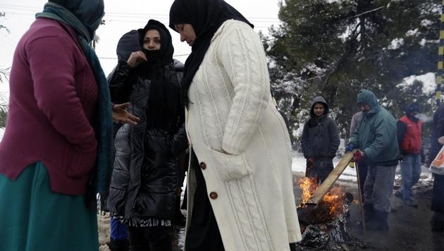 Flüchtlinge in einem Camp nahe Athen (Bild: AP)