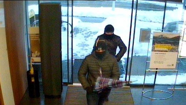 Mit Regenschirm und  Waffe überfielen die Täter die Bank. Drei Tage später klickten Handschellen (Bild: Polizei)