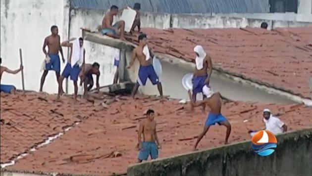 Gefangene, die Steine und andere Gegenstände von den Dächern werfen (Bild: APA/AFP/TV PONTA NEGRA SBT/HO)