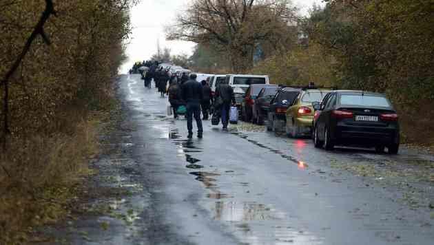 Autokolonne und wartende Menschen bei einem Checkpoint in Sajzewe in der Region Donezk (Bild: APA/AFP/ALEKSEY FILIPPOV)