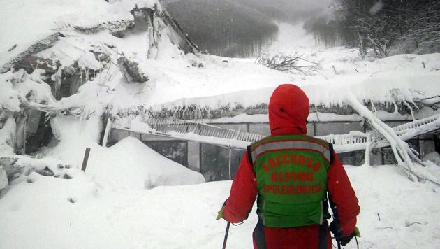Ein Helfer vor dem verschütteten Hotel (Bild: AP)