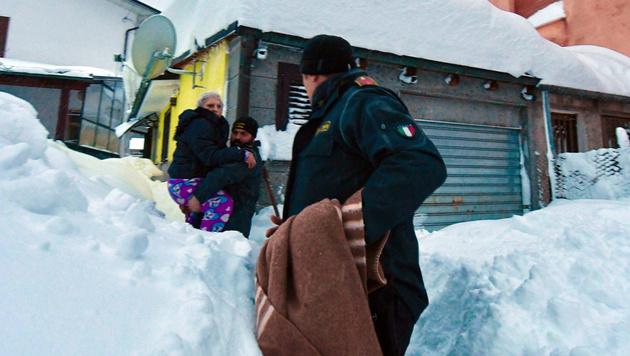 Helfer befreien eingeschlossene Menschen. (Bild: AP)