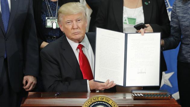 Donald Trump zeigt das Dekret, welches den Mauerbau an der US-Grenze zu Mexiko anordnet. (Bild: AP)