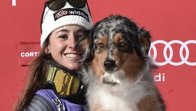 Süß: Sofia Goggia posiert nach Platz zwei in der Cortina-Abfahrt mit ihrem Hund am Podest. (Bild: AFP)