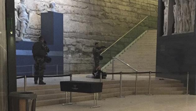 Dieses Bild zeigt den Louvre-Angreifer auf dem Boden liegend, neben ihm zwei Soldaten. (Bild: AP)