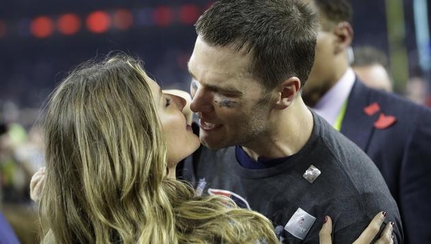 Nach seinem 5. Super-Bowl-Triumph gibt's für Tom Brady einen Kuss von seiner Frau Gisele Bündchen. (Bild: AP)