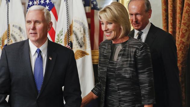 Vizepräsident Mike Pence (li.) hob Betsy DeVos ins Amt. (Bild: AP)