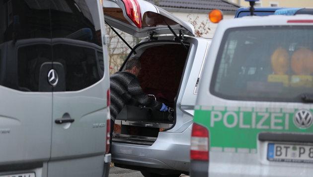 Ein Mitarbeiter eines Bestattungsinstituts lädt einen Sarg in den Leichenwagen. (Bild: APA/dpa/Daniel Karmann)