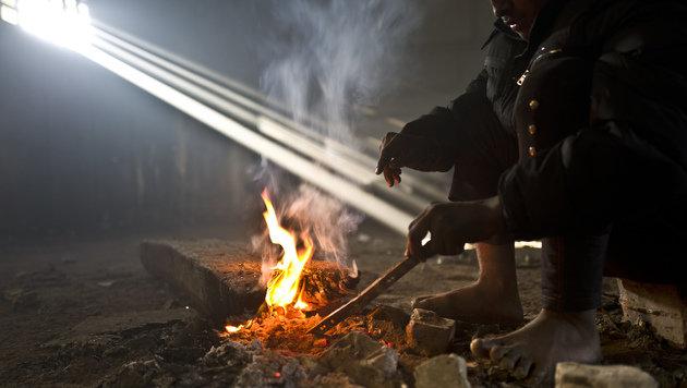 Ein afghanischer Flüchtling wärmt sich in einer ehemaligen Lagerhalle in Belgrad. (Bild: ASSOCIATED PRESS)