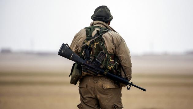 Ein Mitglied der von den USA unterstützten Anti-IS-Allianz in Syrien steht nahe Rakka Wache. (Bild: AFP)